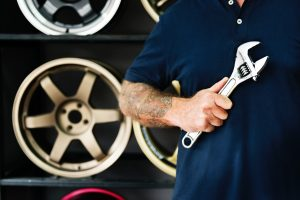 man holding wrench with wheels in front of wheel display
